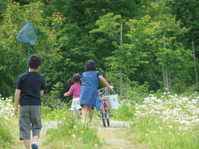 保養の様子。自転車を押す子ども、虫とり網をもつ子ども。