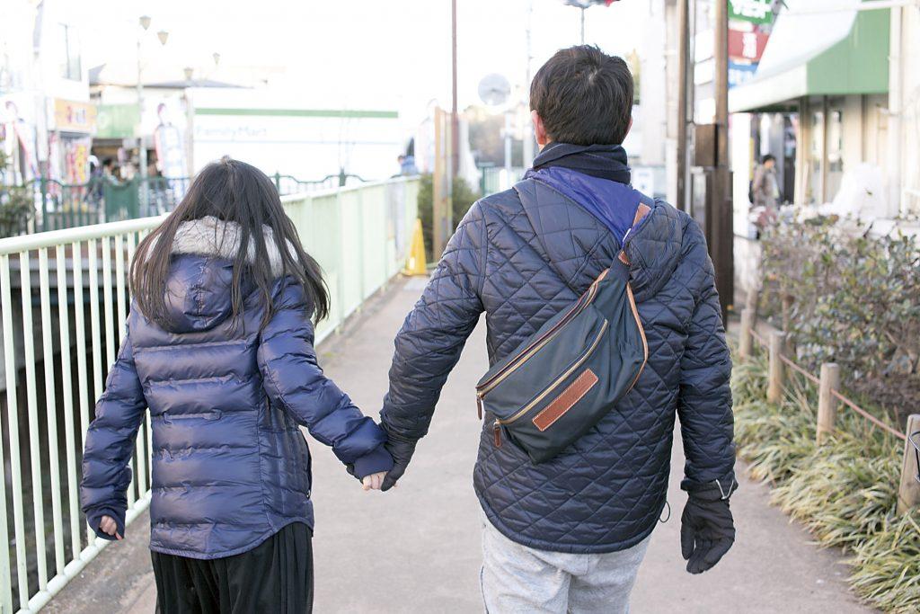 手をつないで歩く父と娘の後姿