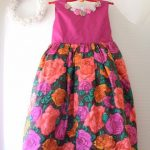 鮮やかなピンクと花柄の生地の子ども用ドレス