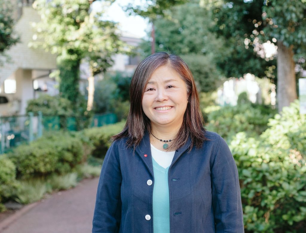 黒田さん正面。後ろには公園の緑がみえる。