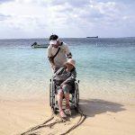 ヘルパーと旅する笑顔の車いすの女性。砂浜には車輪の跡。バックには美しい海が。