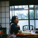 こたつにはいっている女性の横顔。開けられた障子、閉めた窓の向こうに緑がみえる