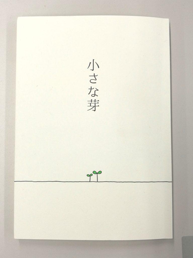 エッセイ集『小さい芽』の表紙。緑の小さい芽がでている絵